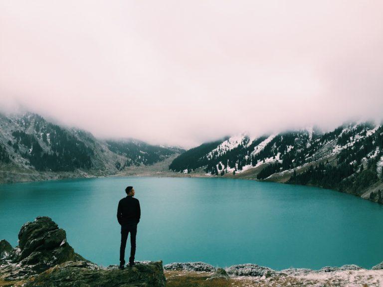 man die aan het denken is terwijl hij uitkijkt naar een valley gevuld met water