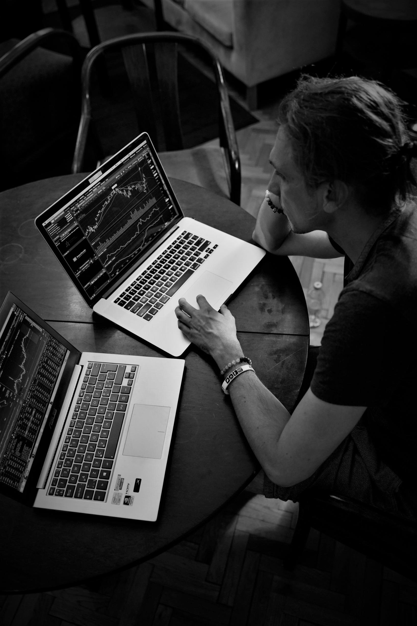 man chter twee laptops aan het beleggen