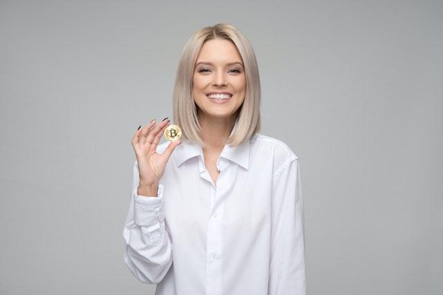blank vrouw in wit thirt die een bitcoin vasthoudt
