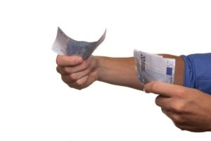 persoon met een handvol geldbiljetten die hij uitleent