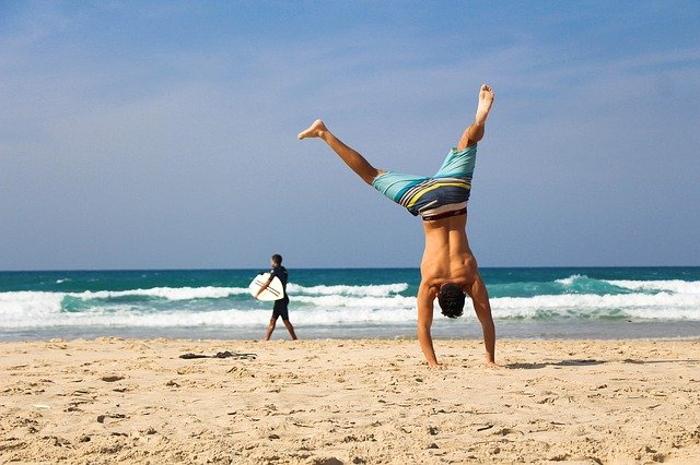man doet een handstand op het strand