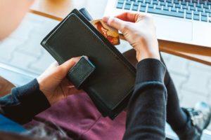 een persoon haalt een pinpas uit zijn portemonnee