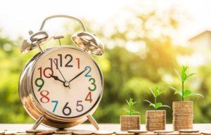 klok met daarnaast telkens een hogere stapel munten dat wil zeggen geld groeit met tijd